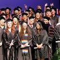 Four rows of smiling students in cap and gown, standing on the Fine Arts stage